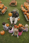 African man talking to children about pumpkins — Zdjęcie stockowe