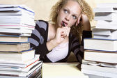 Young woman studying at desk with large stacks of books and notepad — Stock Photo