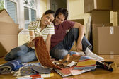 Hispanic couple looking at textile swatches in new house — Stock Photo
