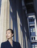 Asian businesswoman standing next to columns — Stock Photo