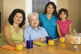 Wielopokoleniowe hiszpanin kobiece członków rodziny uśmiechający się przy stole śniadanie — Zdjęcie stockowe