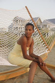 African woman sitting in hammock at beach — Stock Photo