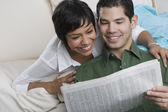 Hispanic couple reading newspaper — Stockfoto