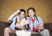 Two young men cheering on sofa with football — Stock Photo