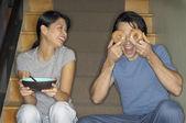 Multi-ethnic couple joking around on stairs — Stock Photo