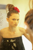 Woman with hair up looking in mirror — Stock Photo