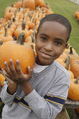 Portrait of African boy holding pumpkin — Stock Photo
