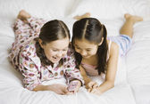 Two girls looking at cell phone on bed — Stock Photo