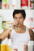 Asian man drinking glass of water — Foto de Stock