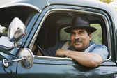 Middle-aged Hispanic man sitting in classic car — Stock Photo