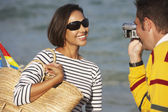 Indian man video recording girlfriend at beach — ストック写真