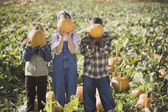 Three children holding pumpkins in pumpkin patch — Stok fotoğraf