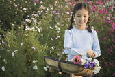 Asian girl holding basket of wildflowers — Stock Photo