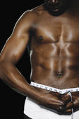 Semi-nude African man measuring waist — Stock Photo