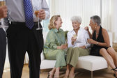 Three senior women talking on sofa at party — Stock Photo