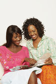 Two African women looking at photographs — Stock Photo
