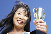 Low angle view of Asian woman holding trophy — Stock Photo