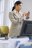 Indian businesswoman using electronic organizer in office — Stock Photo
