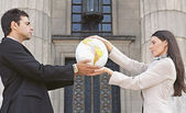 Businesspeople holding globe in front of building — Stock Photo