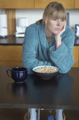 Unhappy woman sitting at breakfast table — Stock Photo
