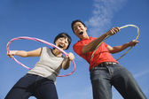 Asian couple playing with hula hoops — Stock Photo