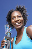 Low angle view of African woman holding trophy — Stock Photo