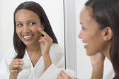 African woman applying face cream in mirror — Stok fotoğraf