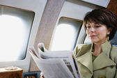 Businesswoman reading newspaper on private airplane — Stock Photo