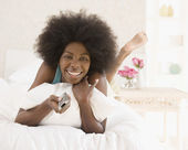 African woman changing channel with remote control — Stock Photo