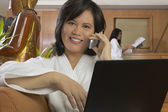 Asian woman in spa bathrobe using cell phone and laptop — Stock Photo