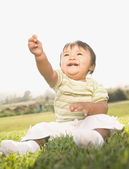 Asian baby sitting in grass — Stock Photo