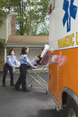 Paramedics putting woman into ambulance — Stock Photo