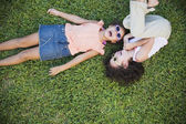 High angle view of young Hispanic sisters laughing in grass — Stock Photo