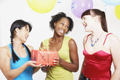 Three woman holding gift at party — Stock Photo