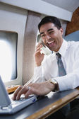 Businessman using telephone on private airplane — Stock Photo