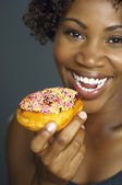 Close up of African woman eating doughnut — Stock Photo