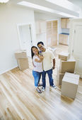 Asian couple taking own photograph in new house — Stock Photo