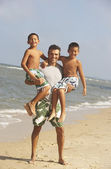 Hispanic father holding two sons at beach — Stock Photo