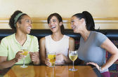 Three women laughing and having cocktails — Stock Photo
