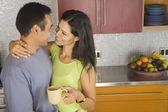 Hispanic couple hugging in kitchen — Stock Photo