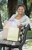 Senior African woman on park bench with shopping bags — Stock Photo