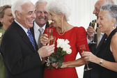 Senior amigos bebiendo champán en fiesta — Foto de Stock
