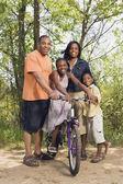 Familia africana con bicicleta en el parque — Foto de Stock