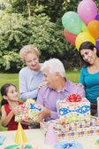 Senior Hispanic man receiving gifts at birthday party — Stock Photo