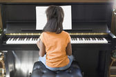Rear view of African girl playing piano — Stock Photo