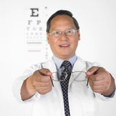 Asian male optometrist offering eyeglasses — Stock Photo