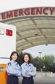 Two Asian female paramedics next to ambulance — Stock Photo
