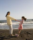Abuela hispana y nieta jugando en la playa — Foto de Stock