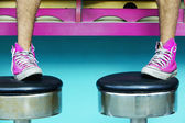 Close up of man's feet in pink sneakers on stools — Stock Photo