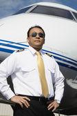 Asian male pilot standing near airplane — Stock Photo